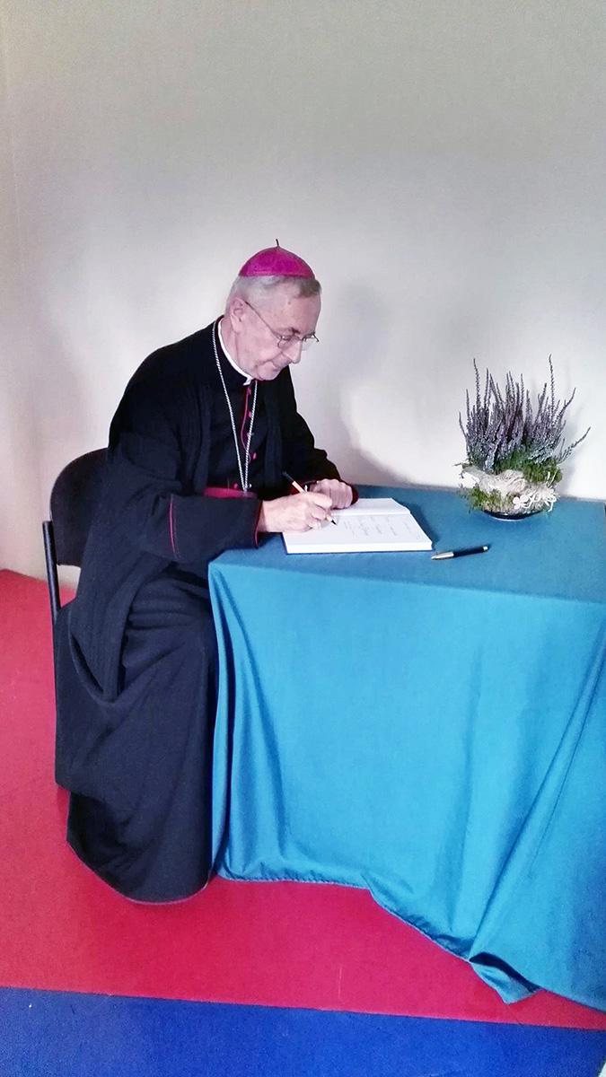 Arcybiskup Stanisław Gądecki wpisuje się do szkolnej Księgi pamiątkowej.